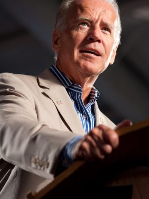 Joe Biden stands behind a podium speaking while wearing a tan suit with an American flag pin as well as a blue and white striped button up shirt.