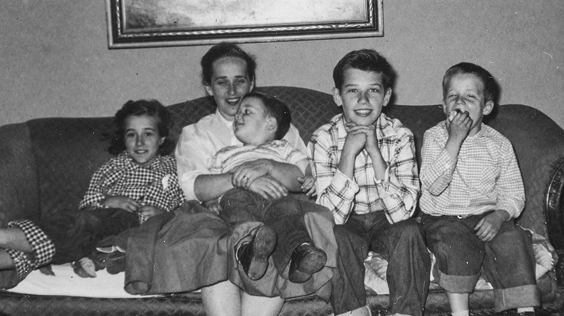 Black and white photo of Joe Biden sitting on a couch with his family.
