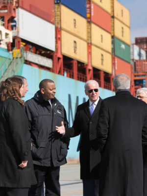 Joe Biden speaks to a group in front of shipping crates