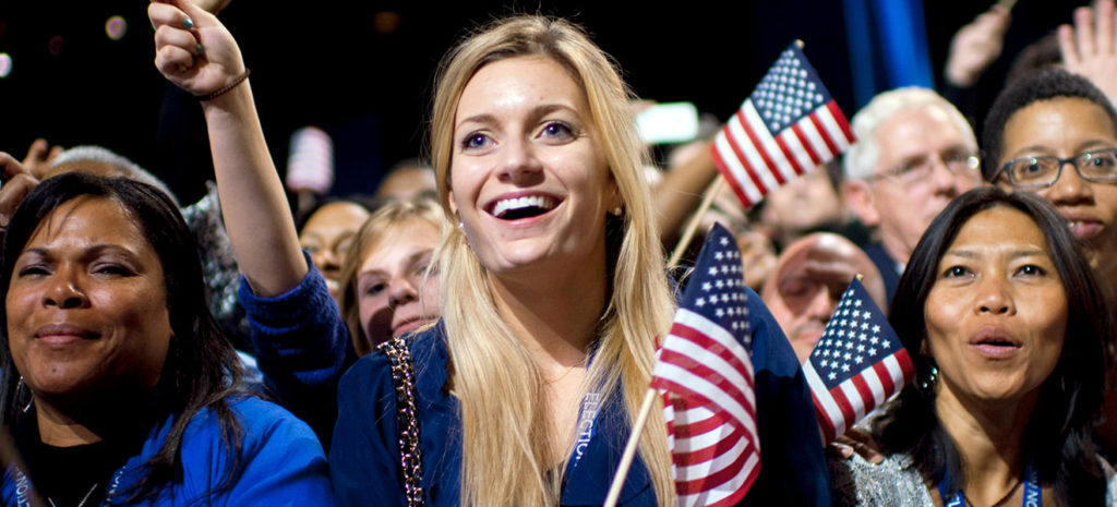 A blonde woman smiles while holding a small American flag. There is a diverse group of individuals in the crowd around her also holding small American flags and cheering.
