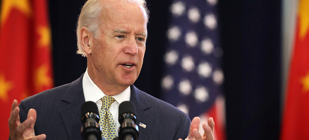 Joe Biden speaks into a microphone while both of his hands are raised in the air reaching his shoulder's height. There are flags behind him in the background.