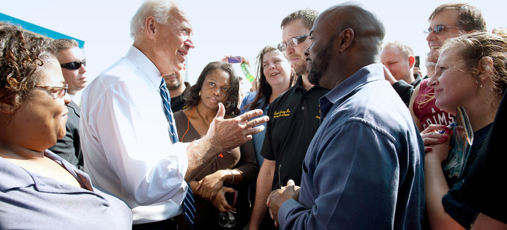 Joe Biden standing outdoors in a white button down shirt with a blue and white striped tie is speaking to a group of diverse workers that are standing around him.
