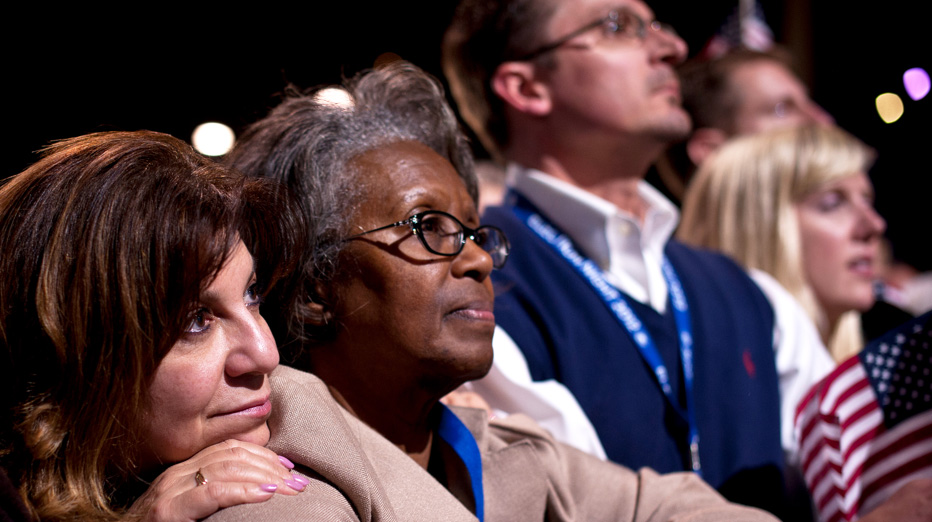 A white woman and an african american woman watch someone speak at a rally. The white woman is resting her head on the other's shoulder.