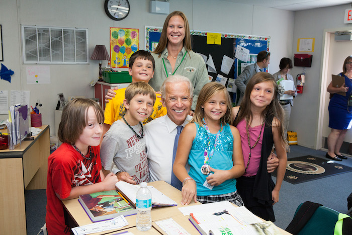 Vice President Biden kneels on a classroom floor with a group of young kids. A teacher looks on and smiles.