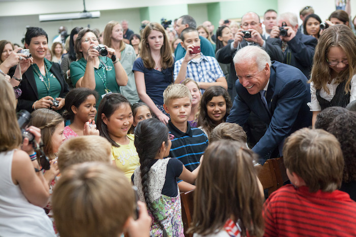 VP Biden shakes hands with a young kid in a classroom, while teachers, staff, and students look on.