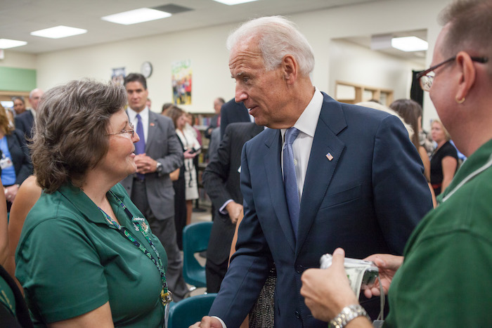 VP Biden shakes hands with a woman at a school.