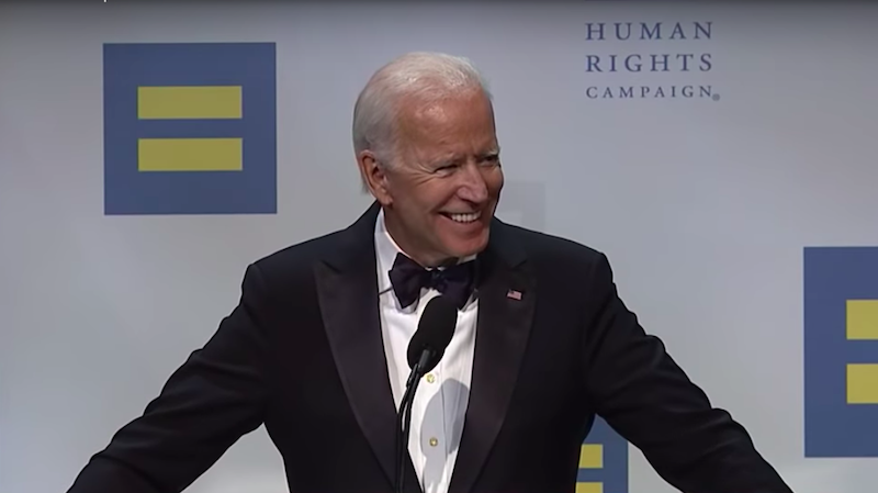 "Joe Biden speaks at a podium in front of a backdrop that reads ""Human Rights Campaign."" He's smiling and wearing a black tuxedo and bow tie."