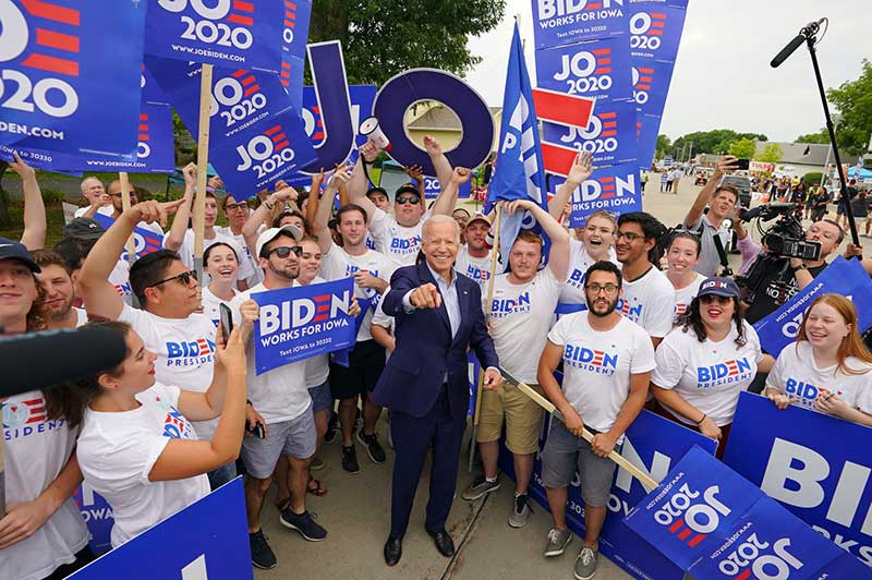 Joe Biden poses for a photo with supporters, who are holding large signs and letters that spell out JOE