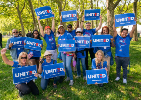 """A group of Joe Biden supporters wear matching blue t-shirts and hold signs that read """"UNITED"""""""