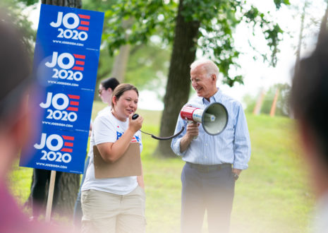 A Joe Biden campaign supporter makes in announcement in a megaphone that Biden is holding. Both people are standing next to a series of JOE 2020 signs.