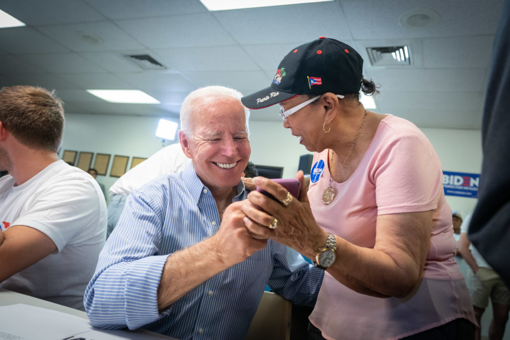 Joe Biden makes calls with a supporter. He is wearing a blue striped shirt, and she is wearing a pink shirt with a black hat.