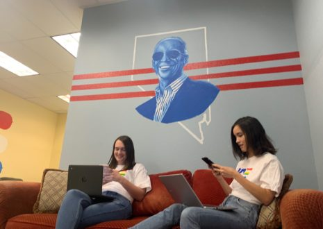 Two campaign supporters sit on a red couch in front of a wall mural of Joe Biden