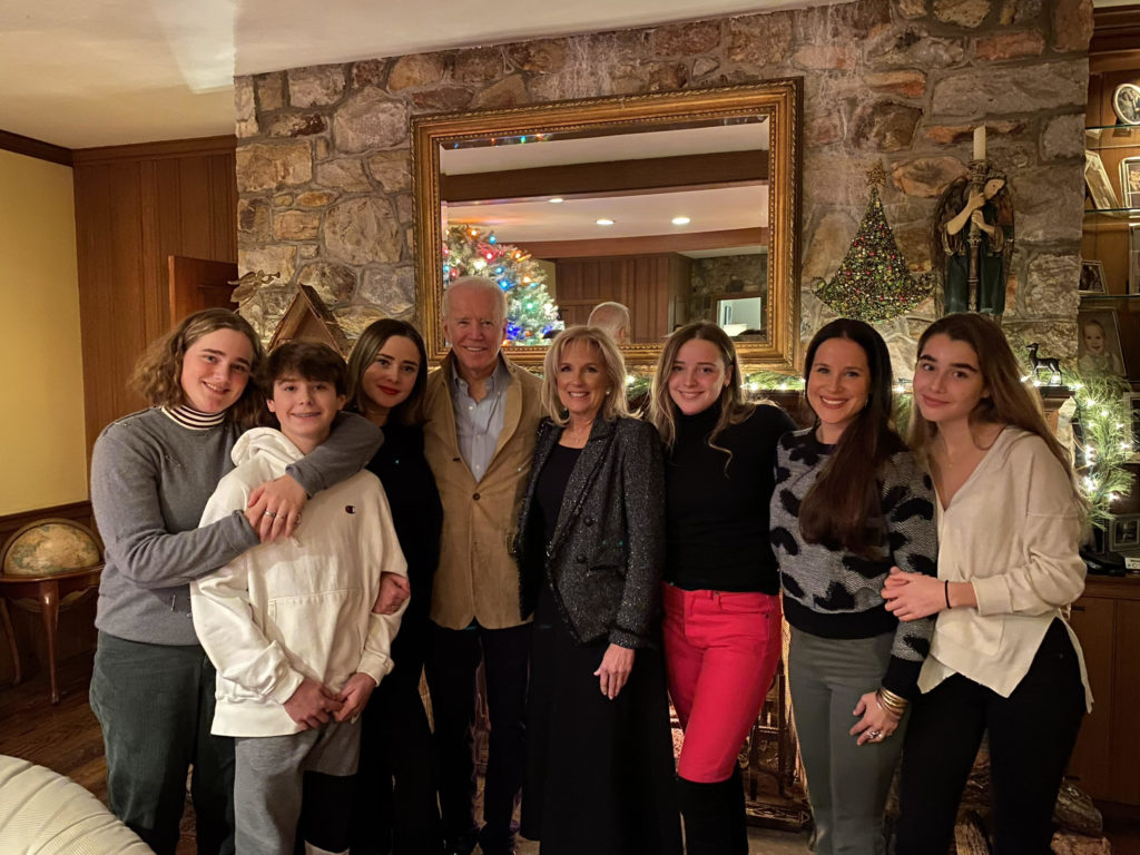 Joe Biden poses with family members in a home adorned with Christmas decorations