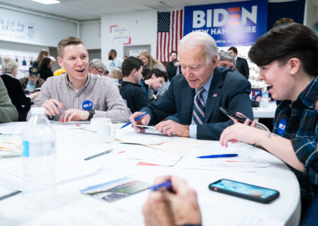 Joe Biden sits at a table with young supporters
