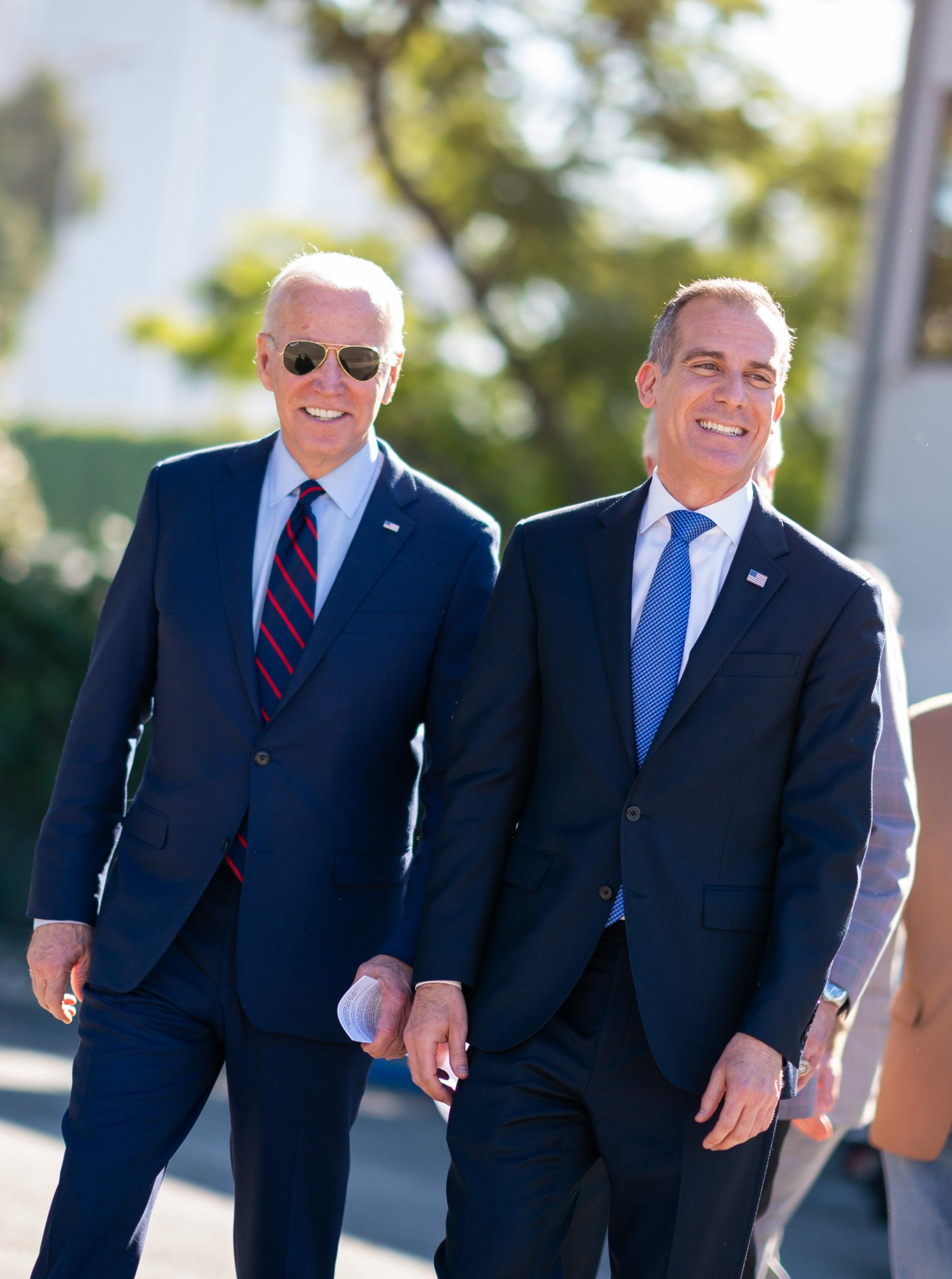 Joe Biden walks with Mayor Eric Garcetti. The two men are wearing suits and American flag lapel pins, and Joe has aviators on.