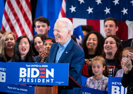 Joe Biden stands at a podium smiling, as supporters behind him cheer on and smile. There are several American flags behind the supporters, and some are holding signs.
