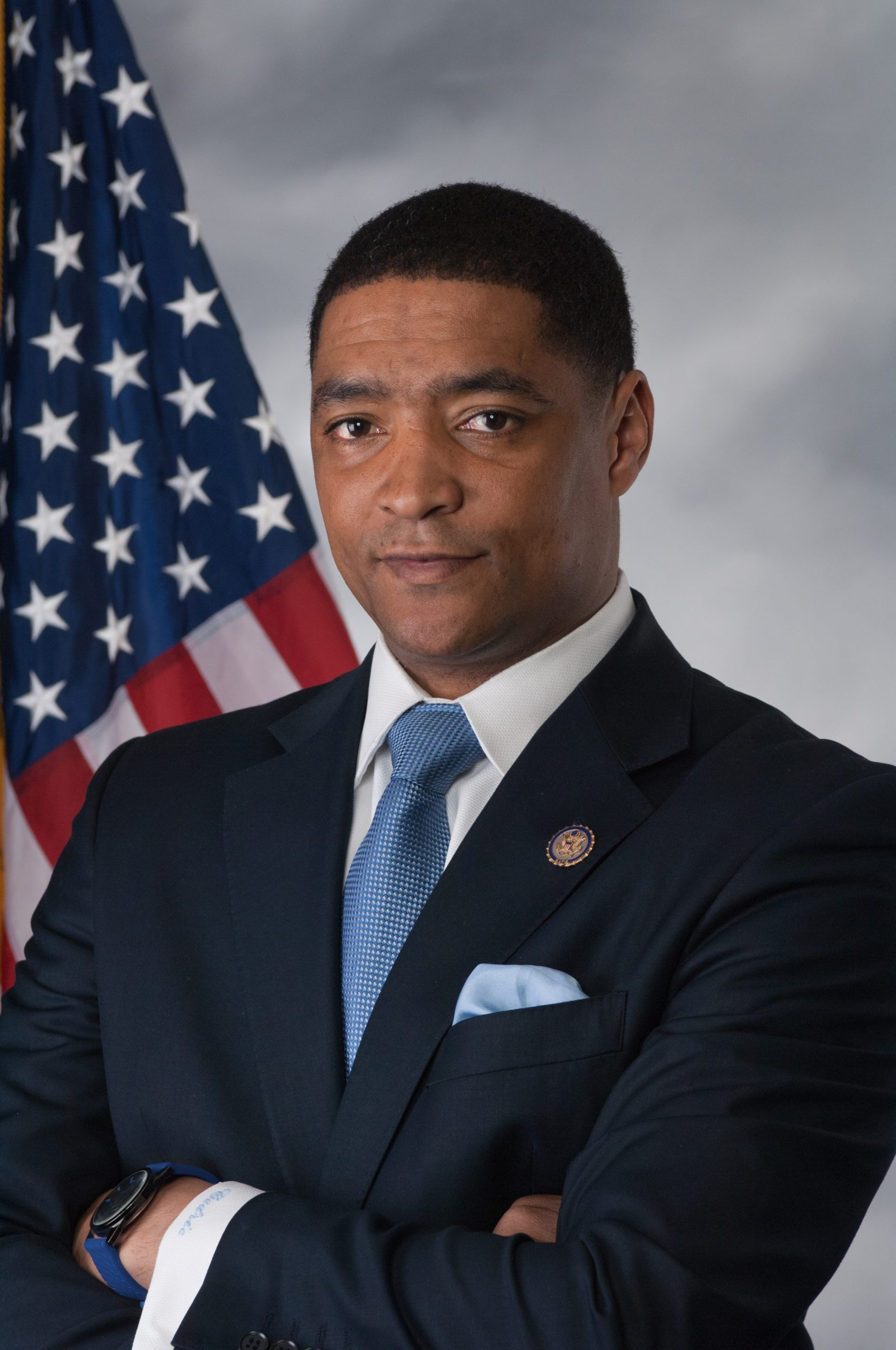 A portrait of Cedric Richmond in front of an American flag