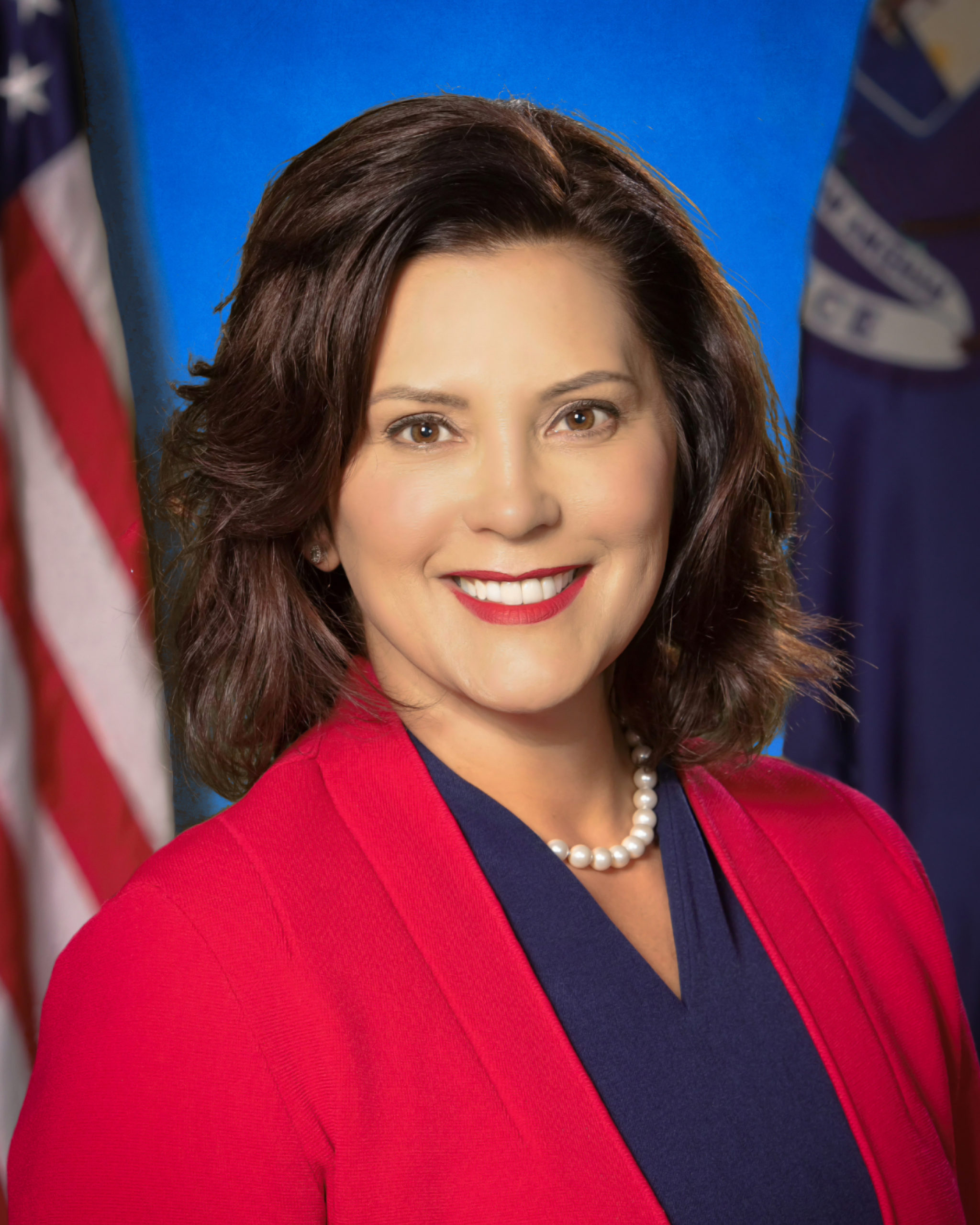 A portrait of Gretchen Whitmer in front of two flags