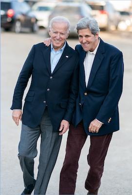 Joe Biden and John Kerry walk together smiling