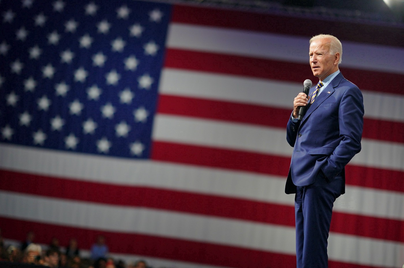 Joe Biden in profile standing and speaking into a hand-held microphone. There is an American Flag behind him.