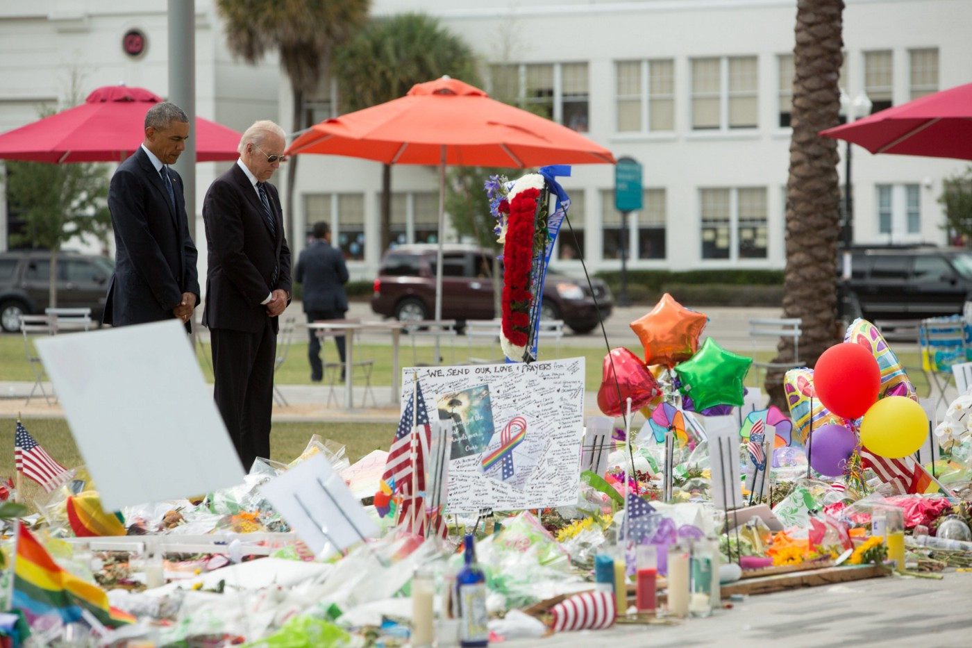 Joe Biden in aviator sunglasses and Barack Obama stand in black suits solemnly at a memorial for the Pulse Nightclub shooting there are colorful balloons, signs, flowers, and candles that people have left to pay their respects.