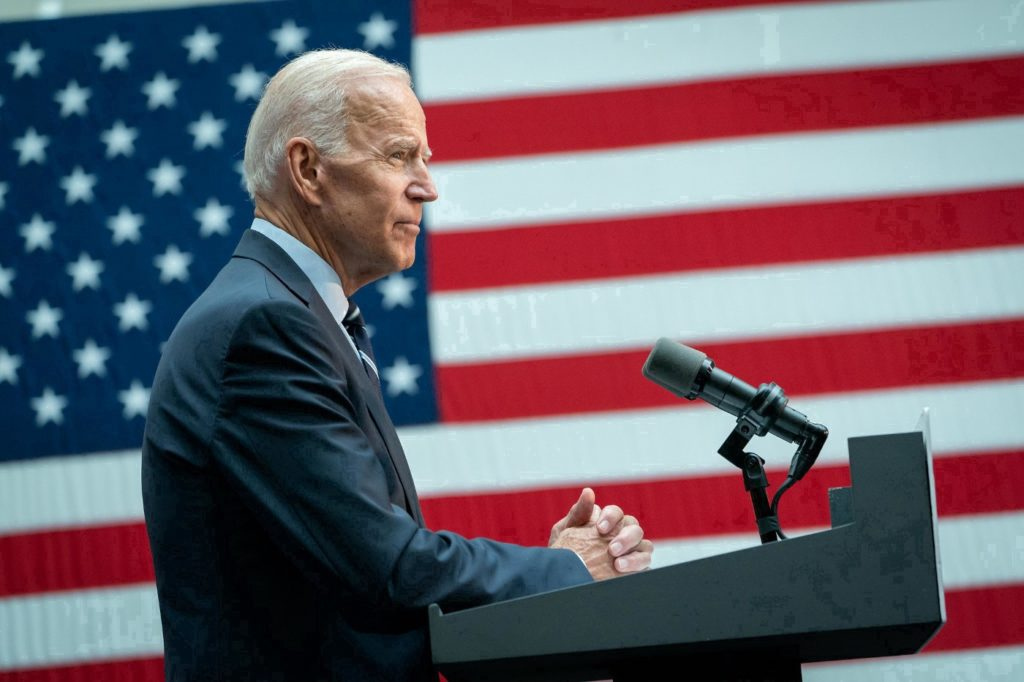 Joe Biden in profile standing at a podium in front of an American flag