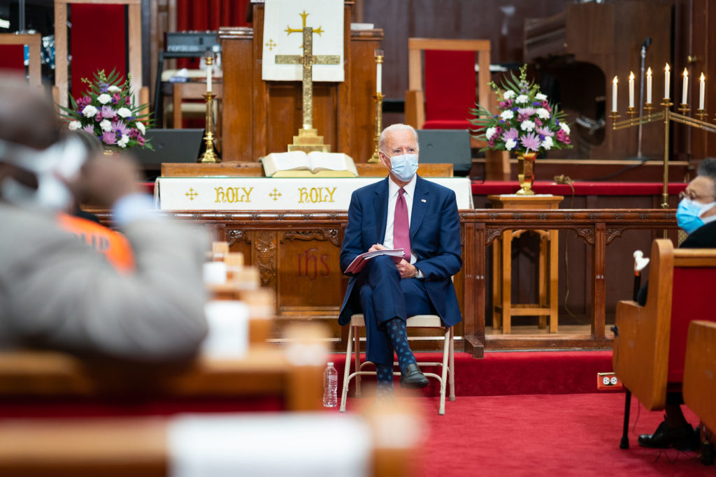 Joe Biden sitting in a church with a mask on, taking notes and listening to patrons. Behind him is the church altar with purple flowers. He is wearing a suit and blue polka-dotted socks.