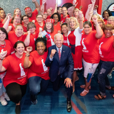 Joe Biden and Dr. Biden amongst of group wearing red. They are all looking at the camera smiling posing with their fists in the air.