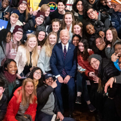 Joe Biden sitting amongst a group of students. They are all smiling at the camera.