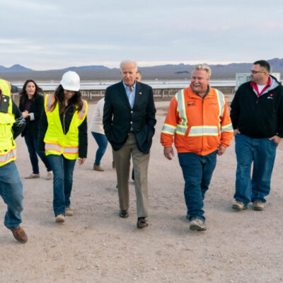 Joe Biden walking on dusty ground with workers in neon vests and hard hats.