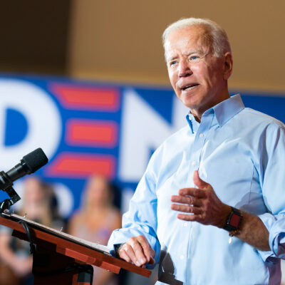 Joe Biden speaking at a podium with a banner in the background with the Biden logo