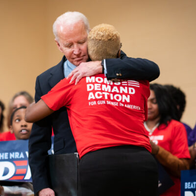 "Joe Biden hugs a person wearing a ""Moms Demand action for Gun Sense in America"" shirt"