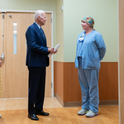 Joe Biden talking to a woman wearing scrubs. They appear to be in a hospital.