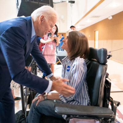 Joe Biden greets a supporter who in a wheelchair.