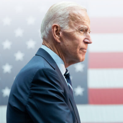 Joe Biden standing in front of the American flag wearing a blue suit