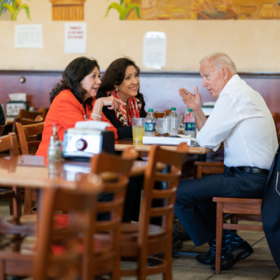 Joe Biden sits at a table in a restaurant talking to two women. They have bottles of water, other beverages, ad a binder on the table.