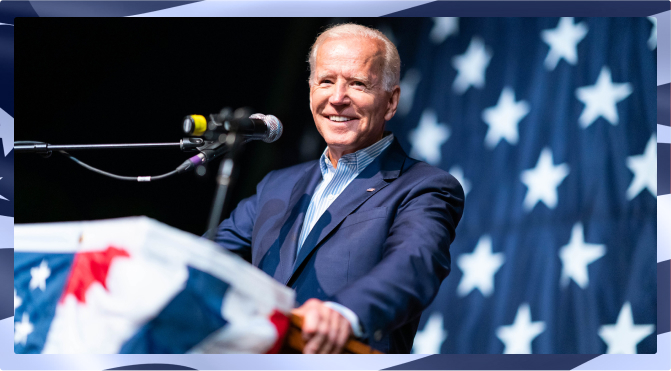 Joe Biden smiling and standing behind a podium. The stars of the American Flag are behind him.
