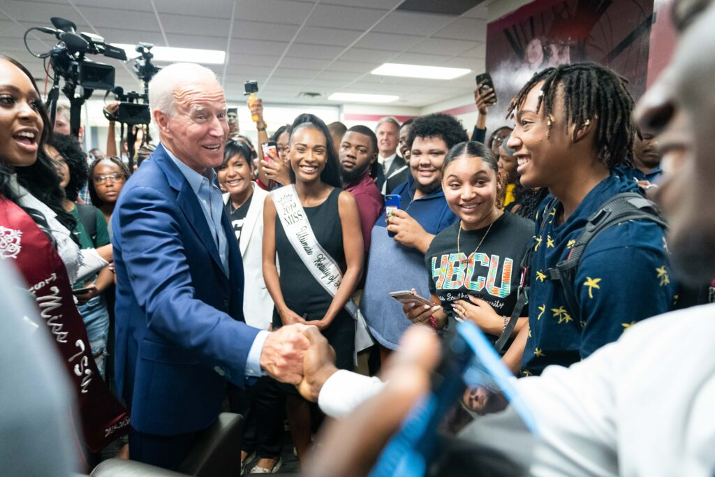 Joe Biden shakes hands with a young man while surrounded by young students