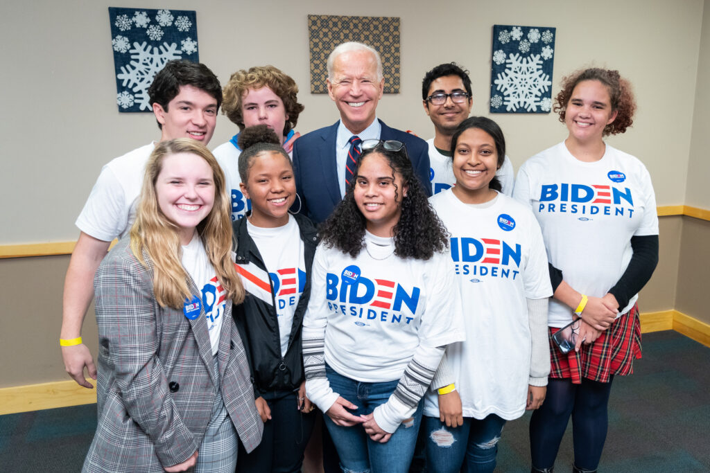 Joe Biden posing with a group of young people who are all wearing white campaign shirts