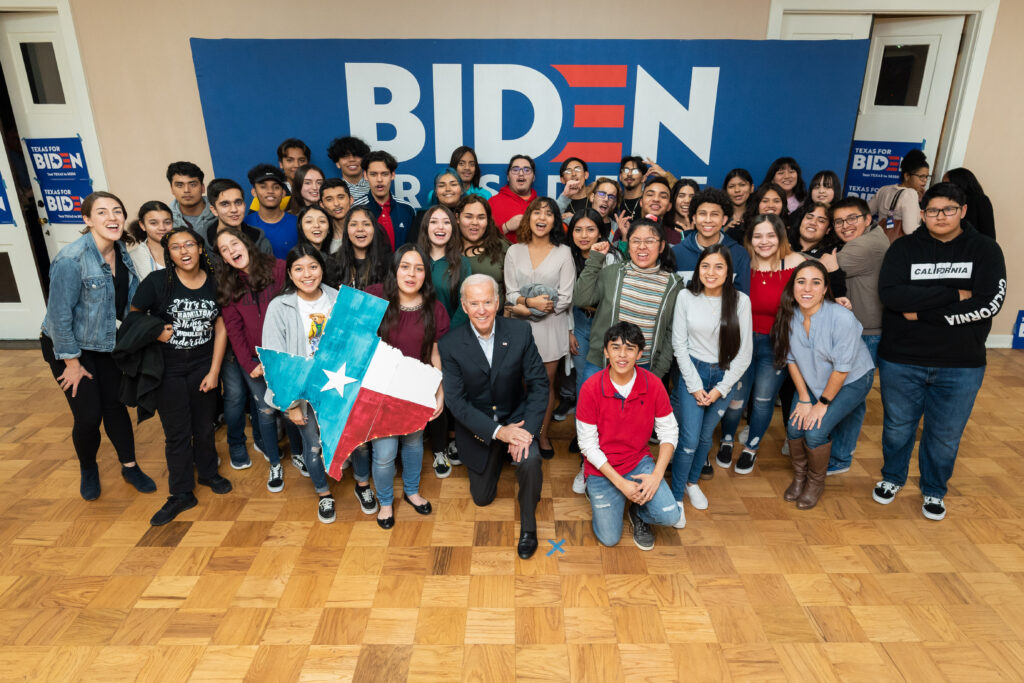Joe Biden poses with a large group of students, one of whom is holding a cutout of Texas