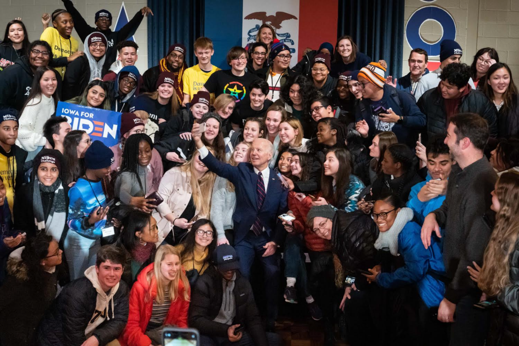 Joe Biden taking a selfie picture with a large group of students