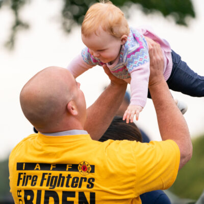 A man in a yellow Fire Fighters for Biden t-shirt holding up and playing with his baby. His back is to the camera.