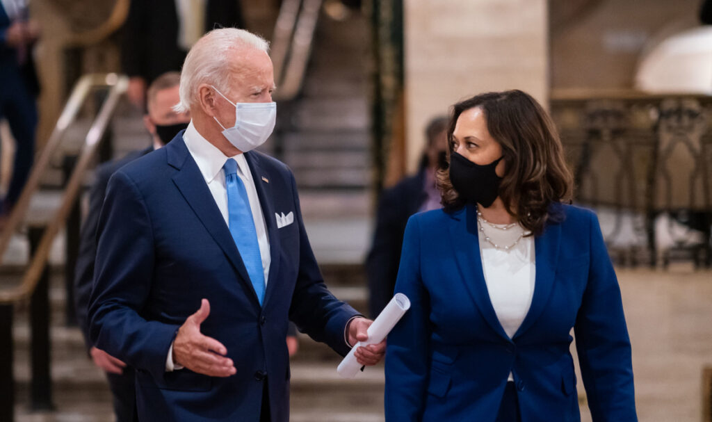 Joe Biden and Kamala Harris walking through the lobby of a building. They are both wearing suits and masks. Joe is holding some rolled up papers in one hand.